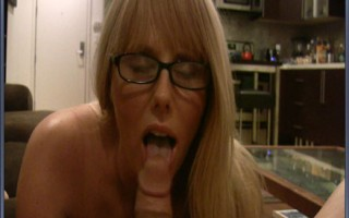 Blue eyed blonde MILF with big melons sucks a big cock in glasses.